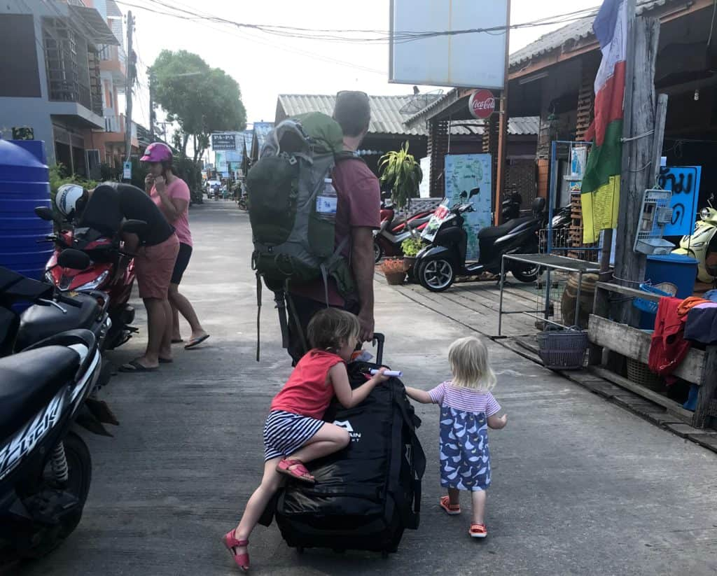 walking along the street in Ko Lanta Thailand with a baby and toddler climbing on to wheeled bag