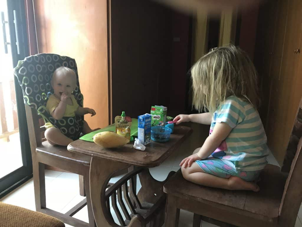 Baby in totseat chair harness and toddler eat breakfast in bedroom in Thailand