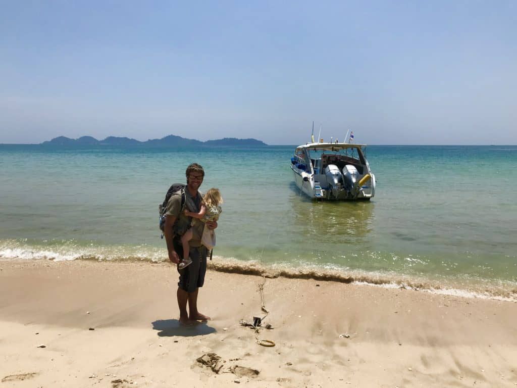 Arrival by boat on a beach in Thailand with a baby in a carrier