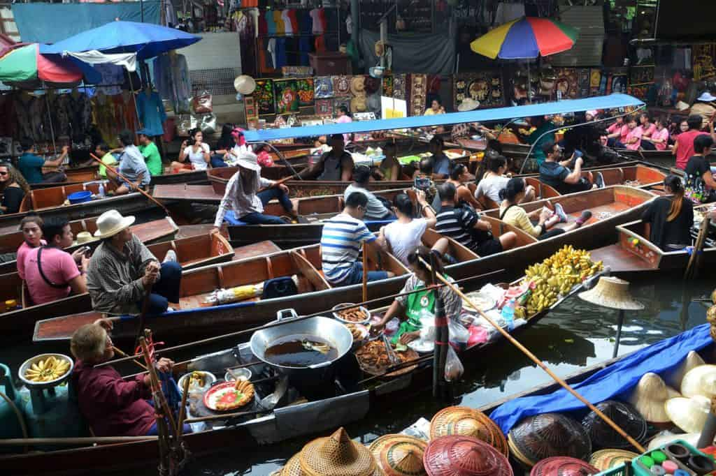 Bangkok 4 day itinerary :day 2 visit the floating markets. Image shows river crowded with wooden boats of floating market