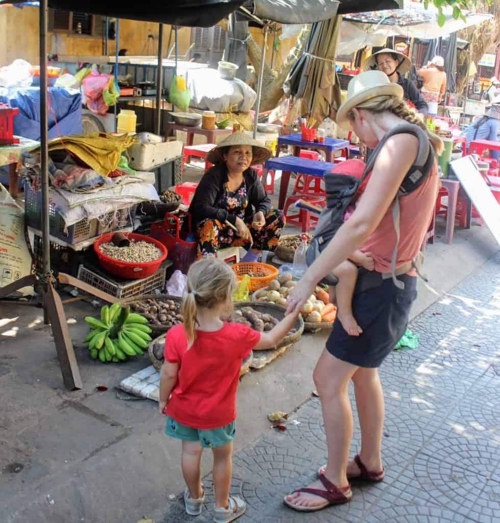 woman looking at fruit stall in Hoi An with kids holding hand and in baby carrier