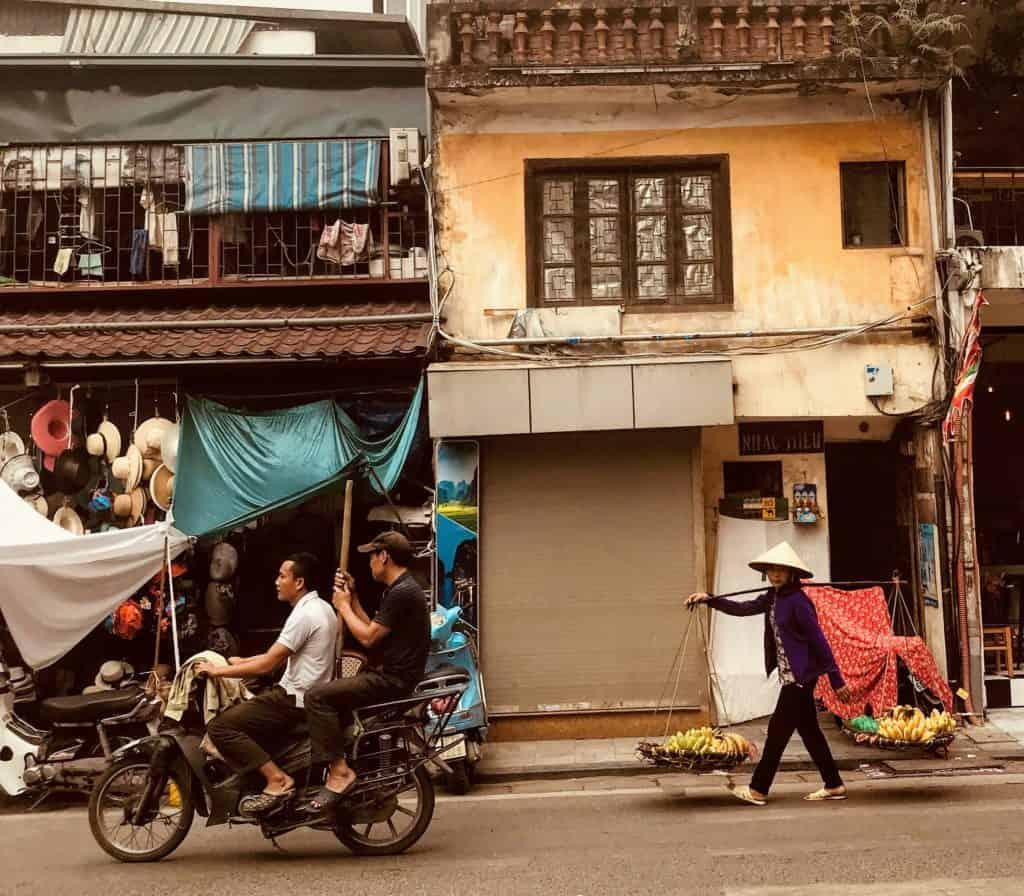 motorbike and street seller in Hanoi, Vietnam with kids