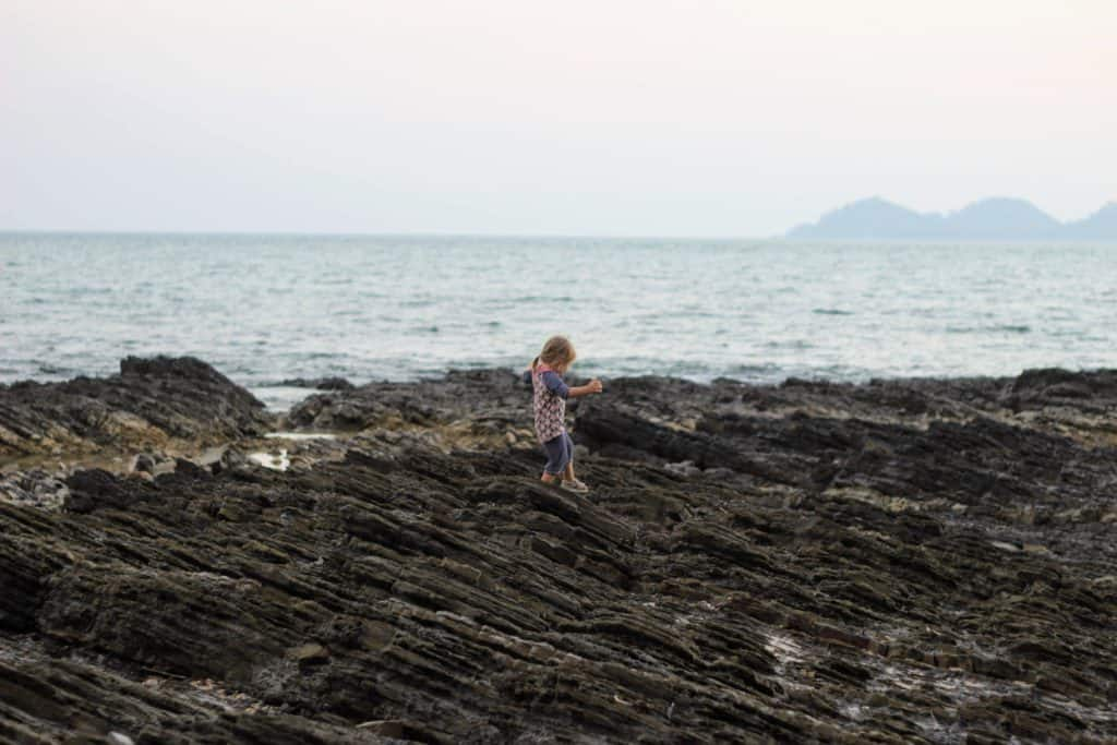 Young girl climbing rocks in Koh Mook