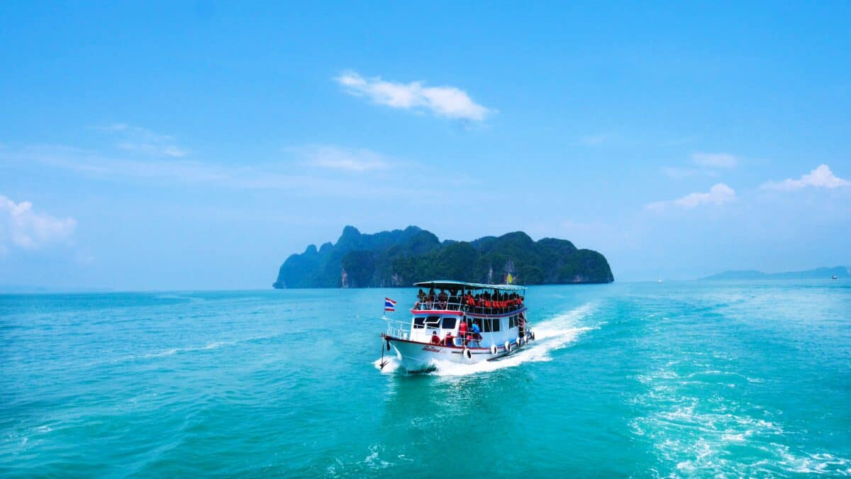 Phuket to Krabi by ferry, passing an island in calm blue seas
