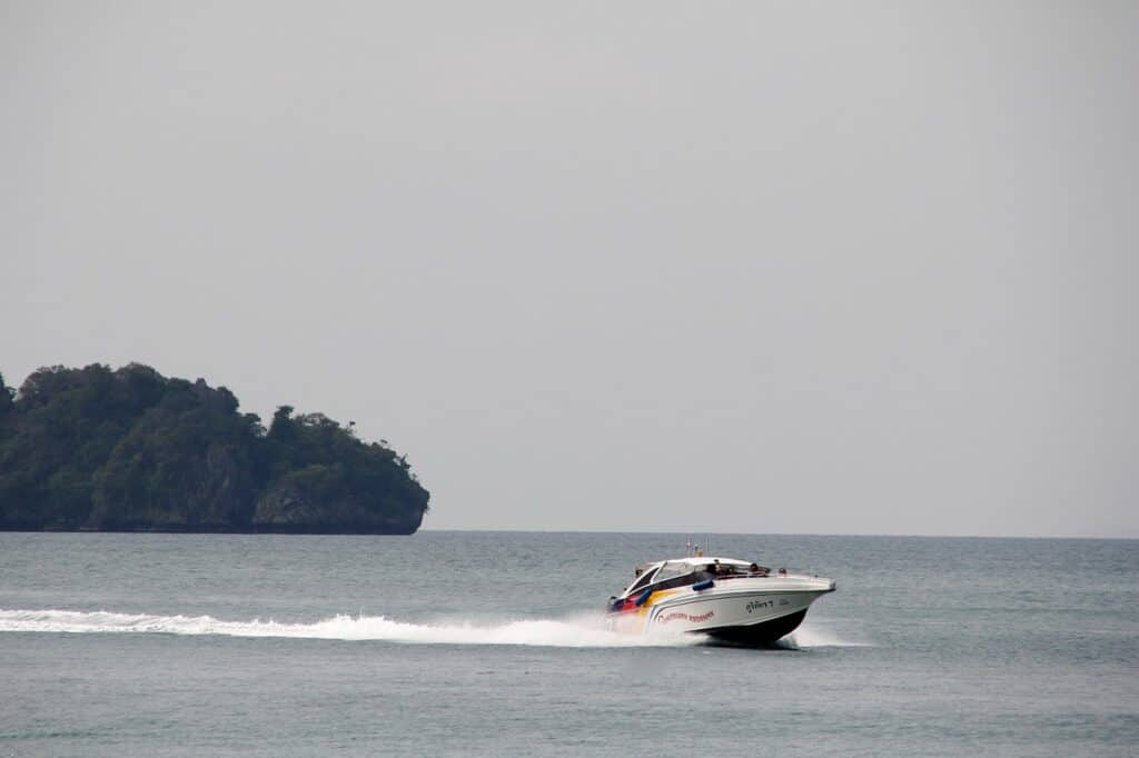 Speedboat passing an island on calm seas. How to get to Koh Phi Phi