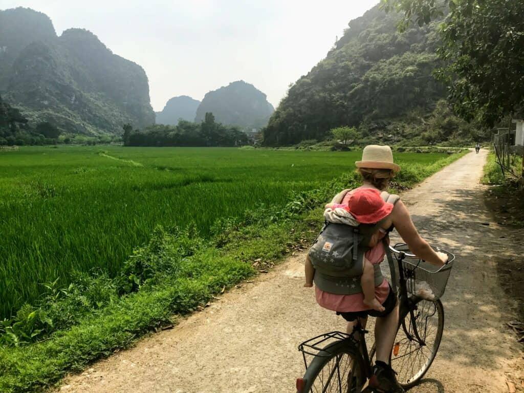 woman cycling past rice paddies on a Vietnam 10 day itinerary
