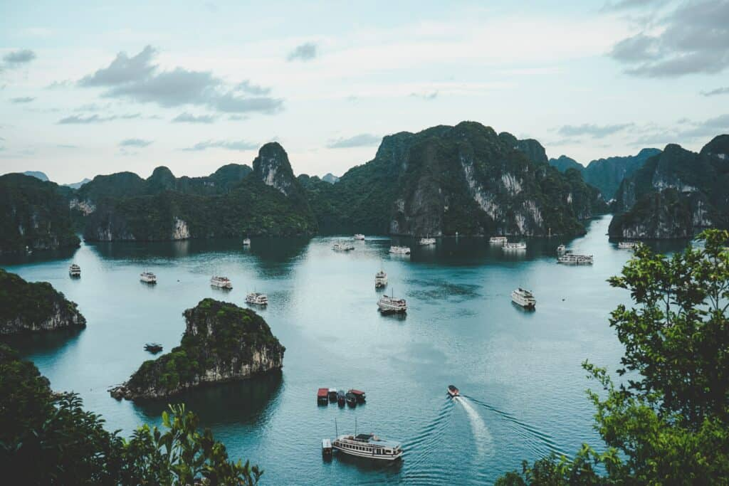 View across water and islands in Halong bay with boats in the water, visited on a Vietnam 10 day itinerary