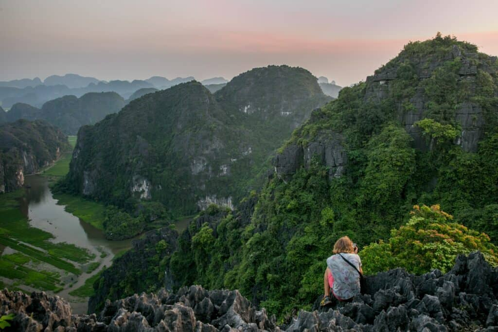 view from the top of mountains in Ninh Binh with person in foreground, part of a 10 day Vietnam itinerary
