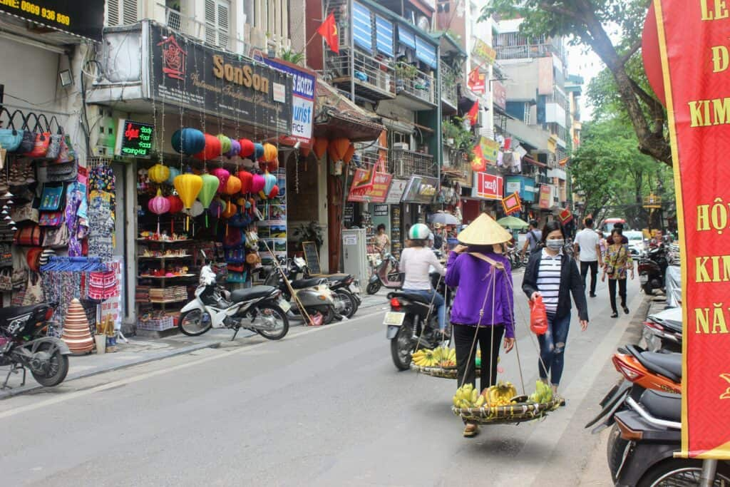 Seller in traditional veitnames hat walks a busy street in Hanoi with kids
