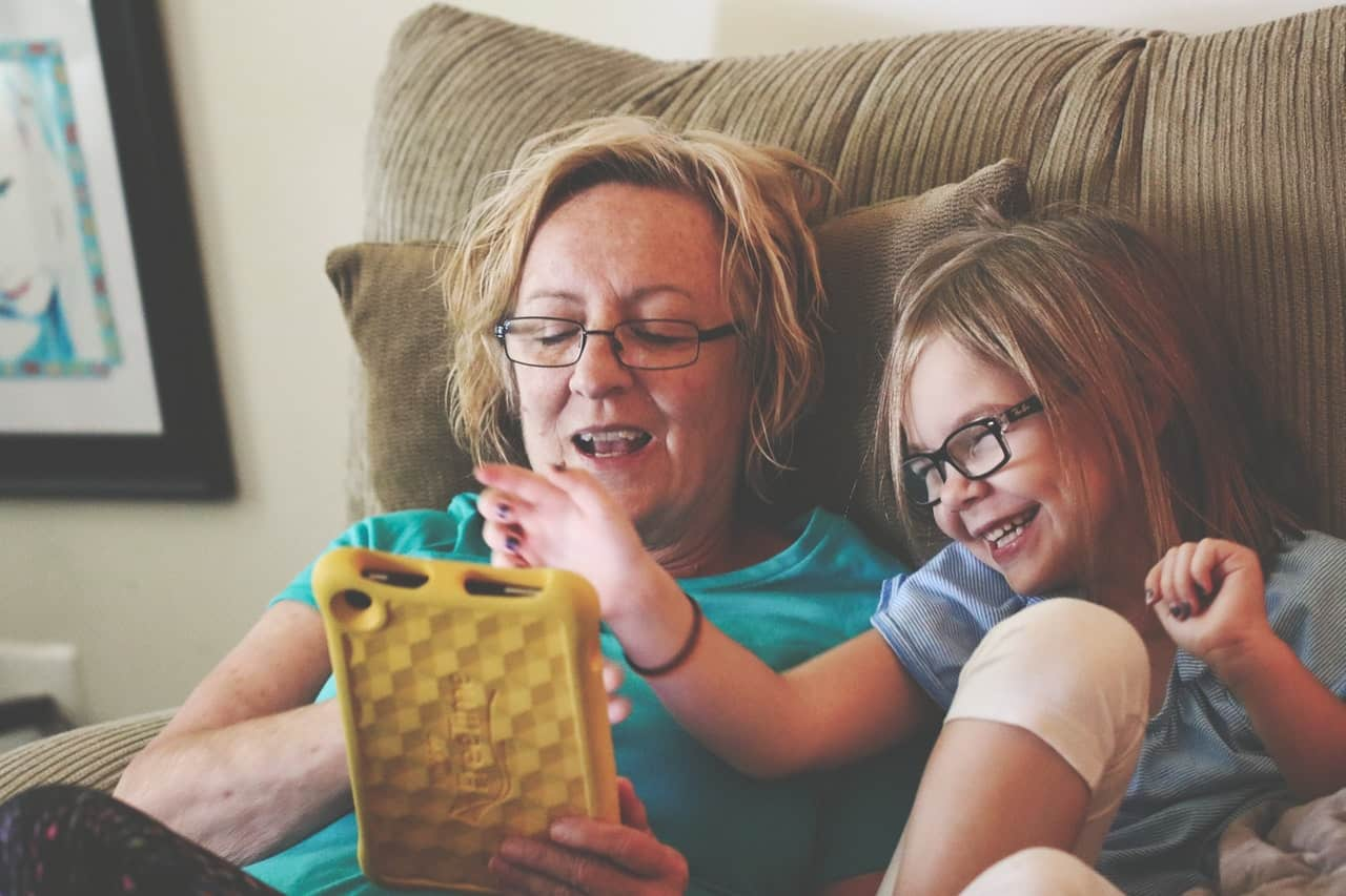 Woman and girl using tablet playing on one of he best apps for toddlers