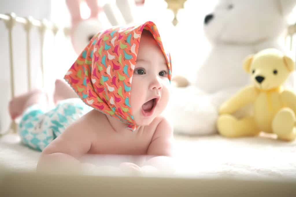 baby with head scarf awake on bed