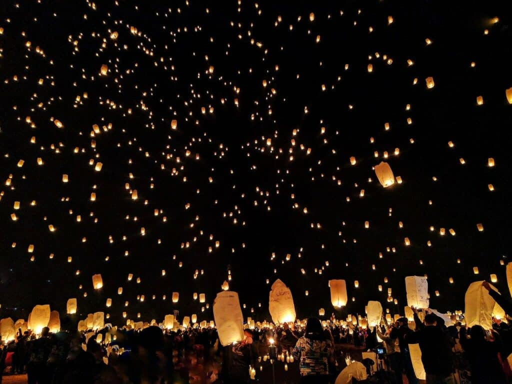 Paper lanterns being set off into the night sky for the Yee Peng Lantern Festival