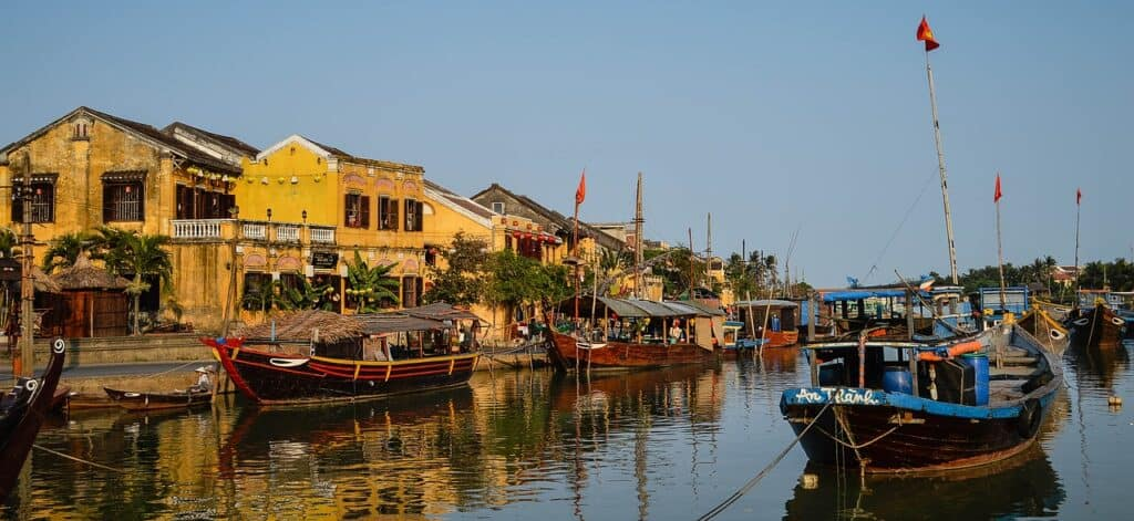 Where to Stay in Hoi An: Boat on the river in front of yellow building