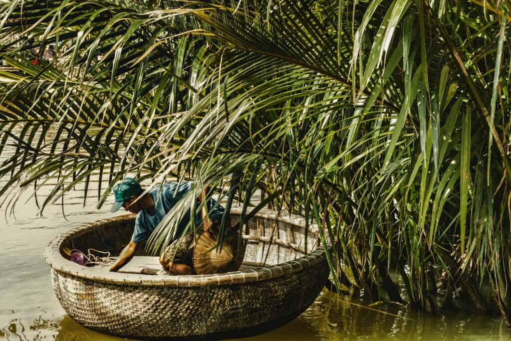 Where to Stay in Hoi An: Man fishing on the river n circular boat