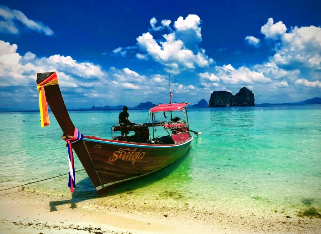 Longtail boat on the beach in Koh Ngai with island behind. Krabi with kids