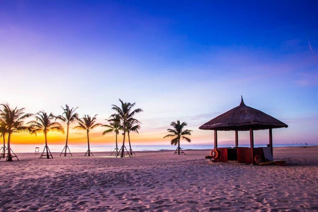 Where to Stay in Hoi An: Beach hut and palm trees on the sand