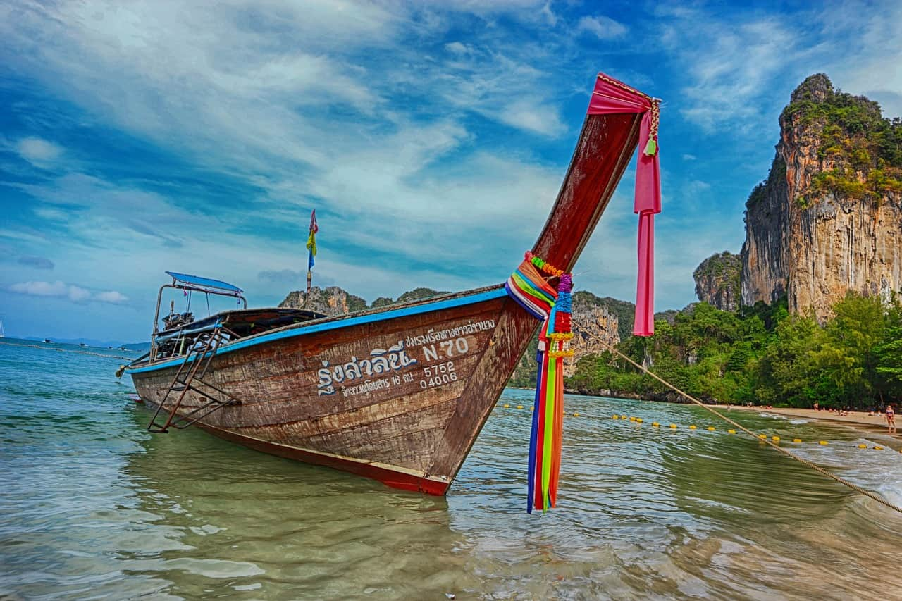 Longtail boat infront of sea and cliff. Krabi with Kids