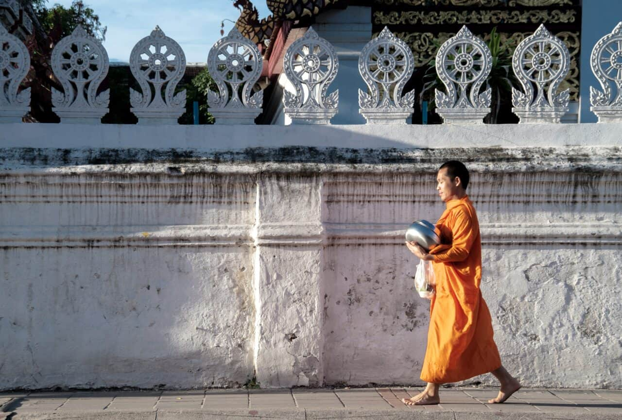 Monk in orange robe wlking infornt of white wall - Chiang Mai itinerary