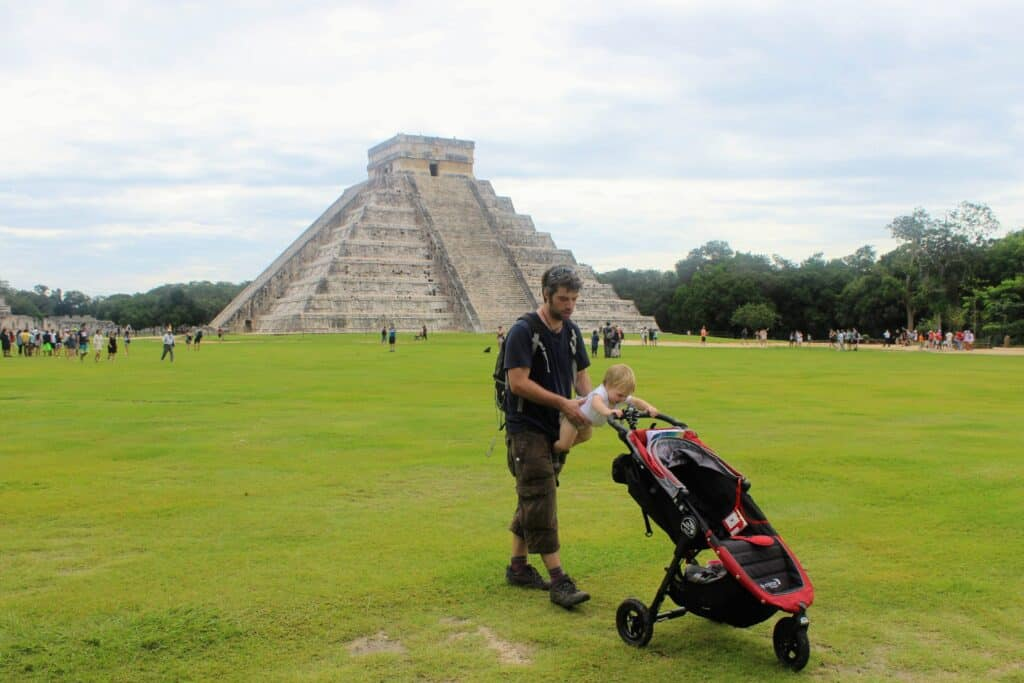 Man baby and stroller in front of Chichen Itza